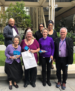 Commission staff dressed in purple outside office